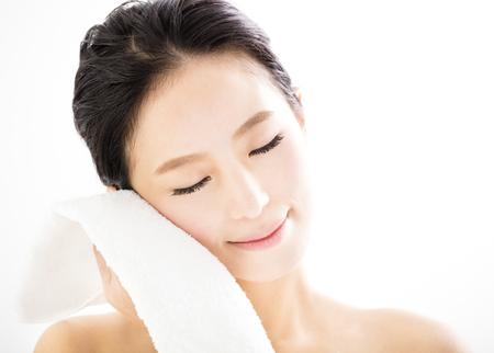 jonge vrouw die haar gezicht schoonmaakt met handdoek