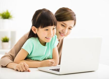 Bonne petite fille regardant un ordinateur portable avec sa mère