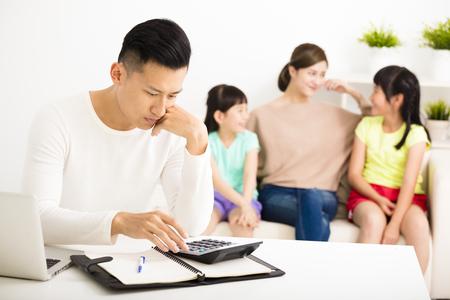 marido y mujer: hombre de estrés cálculo de facturas mientras que la familia se sienta en el sofá Foto de archivo