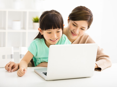 teaching children: happy Little girl looking at laptop  with her mother Stock Photo