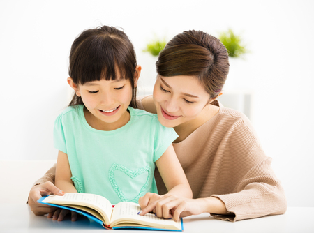 estudiando: Niña feliz que mira el libro con su madre Foto de archivo