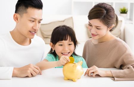 부모와 딸 돼지 저금통에 동전을 넣어