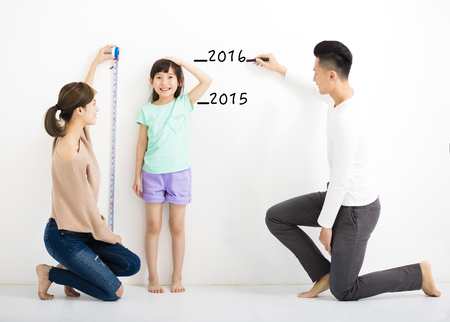 measure height: happy parent measures the growth of   daughter Stock Photo