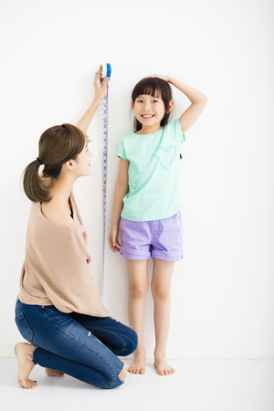 crecimiento: madre mide el crecimiento de su hija Foto de archivo