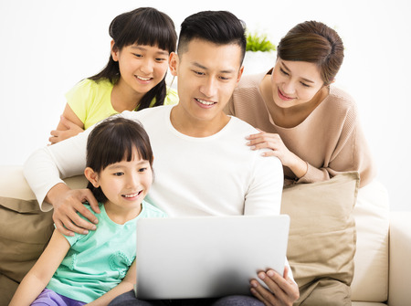 person computer: Happy Attractive Young  Family watching the laptop