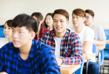 smiling male college student sitting  with classmates Stock Photo