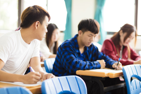 final examination: college student cheating during exam in classroom