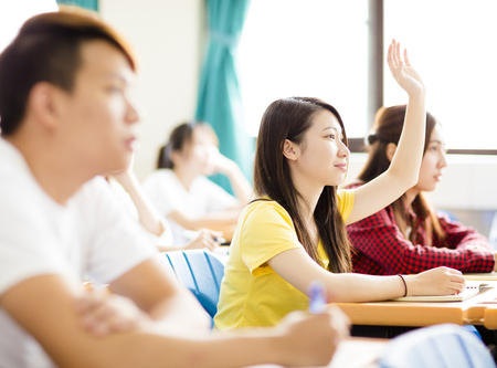 hand raising: female college student raise hand for question in classroom Stock Photo
