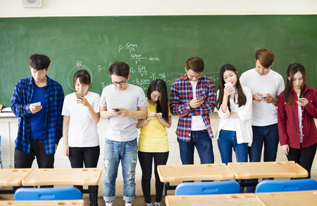Group of students using smart mobile phones in classroom Imagens