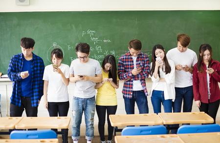 Gruppo di studenti utilizzando i telefoni cellulari intelligenti in aula Archivio Fotografico