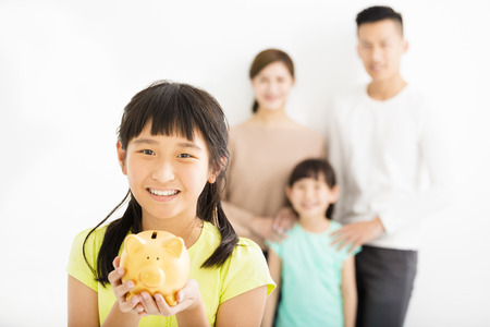 finance concept: little girl showing the piggy bank and family finance concept