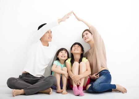 szczęśliwa rodzina siedzi razem i czyniąc znak domu