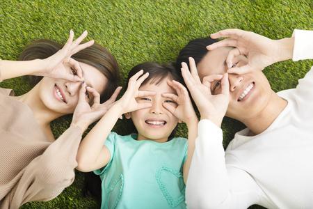 Widok z góry szczęśliwa młoda rodzina leżąc na trawie Zdjęcie Seryjne