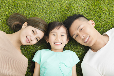 asia children: top view of Happy  Young  Family lying on the grass