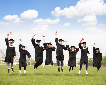幸せな若いグループ卒業一緒にジャンプ 写真素材
