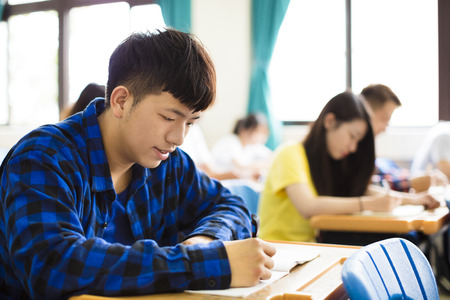 school exam: group of young students writing notes in the classroom Stock Photo