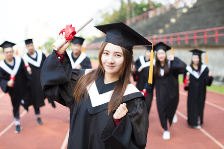 academic robe: happy graduation students with diplomas outdoors