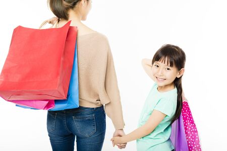 rear view girl: happy little girl shopping with mother