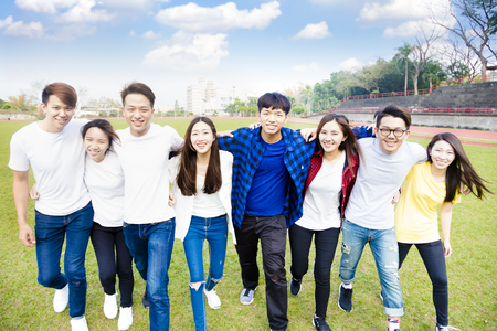 Happy young group of students walking together Stock Photo