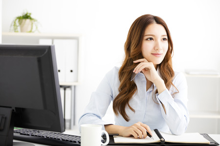 working in office: happy  young business woman working in office Stock Photo