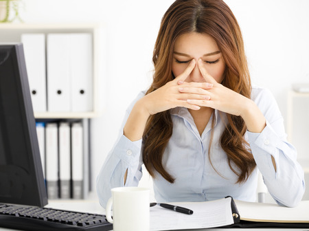 emotional grief: Portrait of tired young business woman working in office