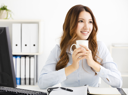 asian businesswoman: Young business woman drinking coffee and looking