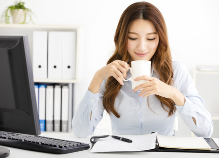 women coffee: Young business woman drinking coffee and looking