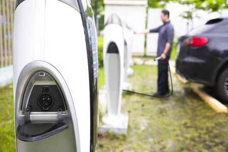 electric station: man operating Power supply station for electric car charging