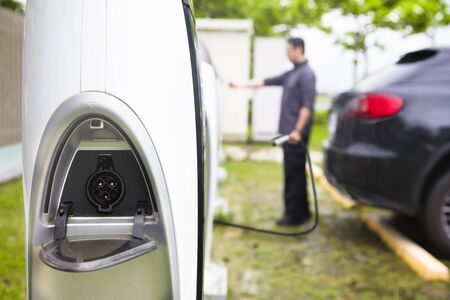 electric power station: man operating Power supply station for electric car charging
