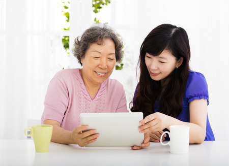aged: happy senior Mother and daughter learning  tablet pc