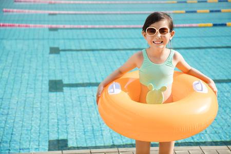 スイミング プールで楽しんで幸せな少女 写真素材