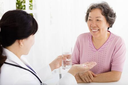 assisting: doctor giving medication and water to senior woman