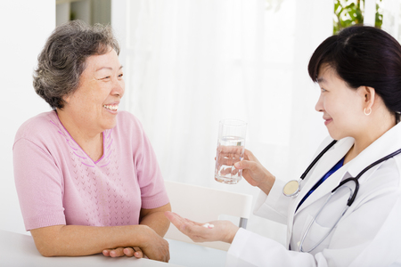 doctor giving medication and water to senior woman