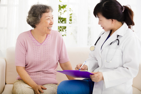 home visit: Nurse Making Notes During Home Visit With Senior woman