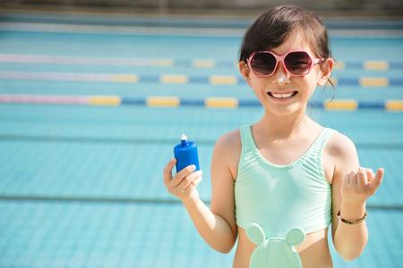 suncare: happy little girl applying sunscreen lotion on nose