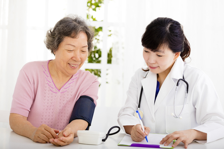 nurse checking senior woman blood pressure Imagens