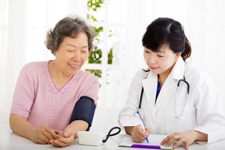medicalcare: nurse checking senior woman blood pressure Stock Photo