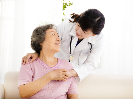 seniors: Nurse holding hand of senior woman in rest home