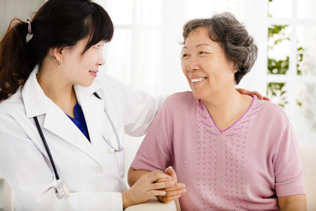 Nurse holding hand of senior woman in rest home