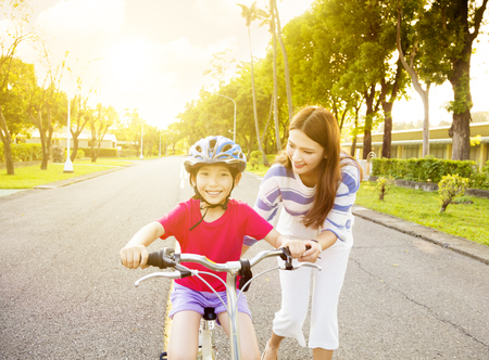 happy little girl with mother practice to riding  bicycle Stock Photo