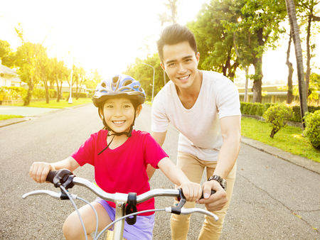 asia people: happy little girl with father practice to riding  bicycle Stock Photo