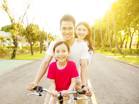 niños en bicicleta: Feliz familia asiática que se divierten en el parque con la bicicleta