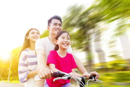 bikes: Happy asian family having fun in park with bicycle Stock Photo