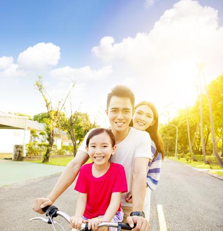 familias jovenes: Feliz familia asiática que se divierten en el parque con la bicicleta