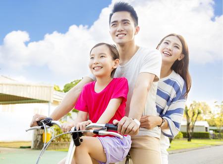 familia: Feliz familia asiática que se divierten en el parque con la bicicleta