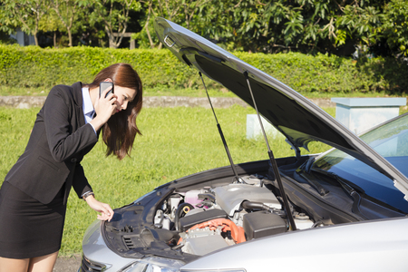 broken telephone: stress business woman calling for help with  car broken concept Stock Photo