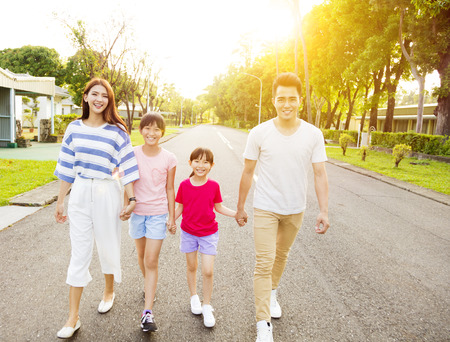 man outdoors: happy asian family walking on the street