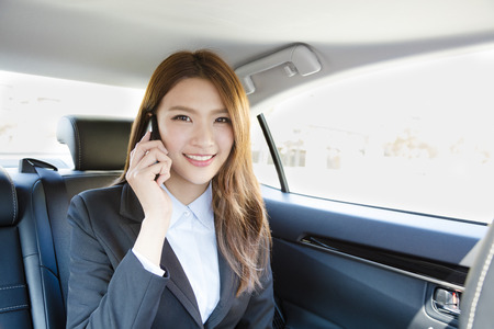smiling Businesswoman inside her car talking on the mobile phone