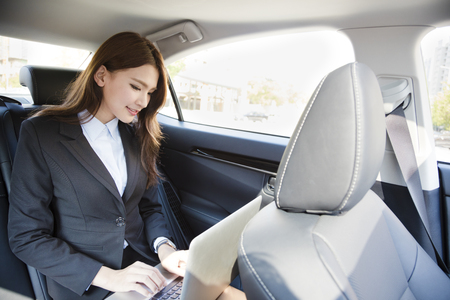 back seat: Businesswoman sitting on back seat of car and working with laptop Stock Photo