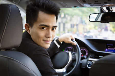 happy young business man driving in the car